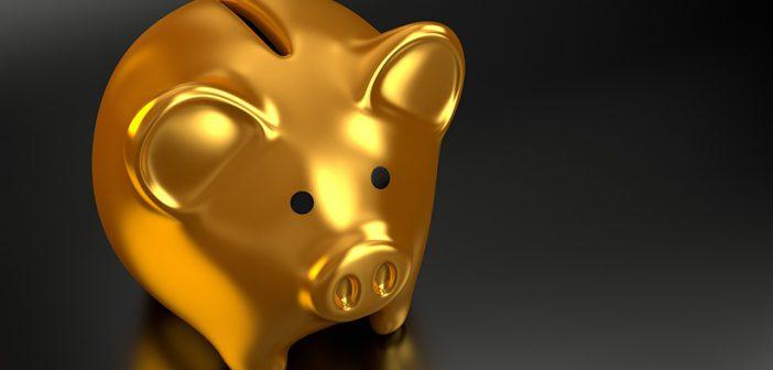 Goldenes Sparschwein auf einem schwarzen Tisch